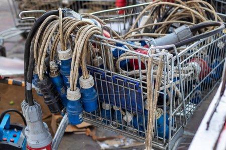 Photo pour De nombreuses fiches de style Iec 60309 avec câbles dans le chariot. Chariot rempli de bougies de tension triphasées à usage industriel. - image libre de droit