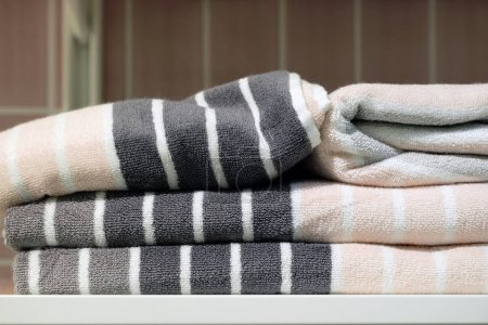 Folded towels, carpet Slippers and bathrobes on the shelf of the wardrobe in the hotel. Bathroom accessories