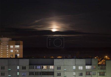 Photo pour Creepy lune dans le ciel nocturne dans le contexte des maisons urbaines et les bâtiments, l'influence de la lune sur l'homme - image libre de droit