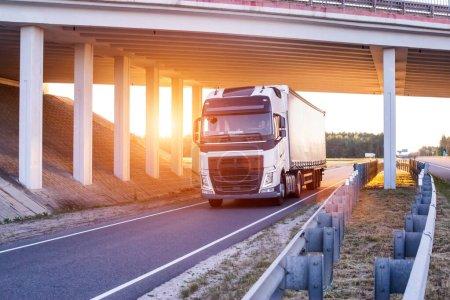 An international driver is carrying goods on a wagon under a bridge. Trucker work concept, work and rest mode, job vacancies, background