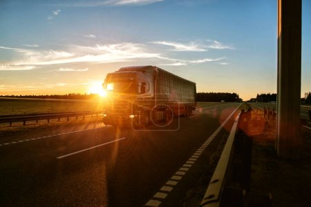 A road train carries a groupage cargo in a semi-trailer against the backdrop of a sunny sunset. Social transportation international, driver internships and hiring, background