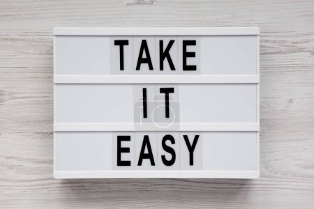 Photo pour 'Take it easy' words on a lightbox on a white wooden surface, top view. Overhead, from above, flat lay. - image libre de droit