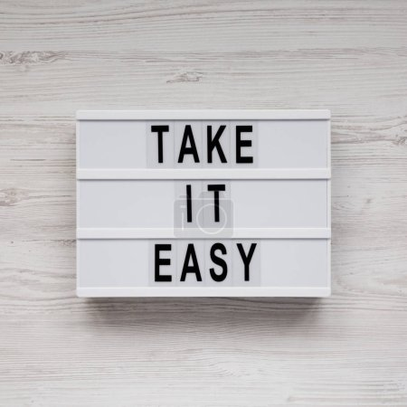 Photo pour 'Take it easy' words on a lightbox on a white wooden background, top view. Overhead, from above, flat lay. - image libre de droit