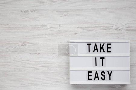 """Photo pour """"Take it easy"""" mots sur une planche moderne sur un fond blanc en bois, vue de dessus. Vue d'en haut, planche à plat. Table des matières. - image libre de droit"""