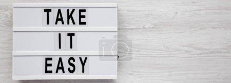 """Photo pour """"Take it easy"""" mots sur une boîte lumineuse sur un fond blanc en bois, vue de dessus. Vue d'en haut, planche à plat. Table des matières. - image libre de droit"""