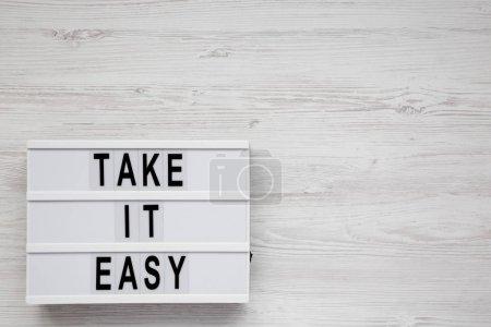 """Photo pour """"Take it easy"""" mots sur une boîte lumineuse sur une surface blanche en bois, vue de dessus. Vue d'en haut, planche à plat. Espace réservé au texte. - image libre de droit"""