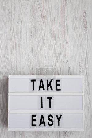 """Photo pour """"Take it easy"""" mots sur une planche moderne sur une surface en bois blanc, vue de dessus. Vue d'en haut, planche à plat. Table des matières. - image libre de droit"""