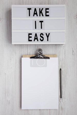 """Photo pour Mots """"Take it easy"""" sur une planche moderne, planche à reliure avec feuille de papier vierge sur fond blanc en bois, vue de dessus. Vue d'en haut, planche à plat. Table des matières. - image libre de droit"""