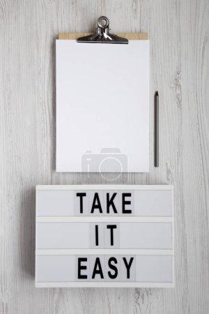 """Photo pour Mots """"Take it easy"""" sur une boîte lumineuse, planche à reliure avec feuille de papier vierge sur fond blanc en bois, vue au-dessus. Vue du haut, d'en haut, à plat. Table des matières. - image libre de droit"""