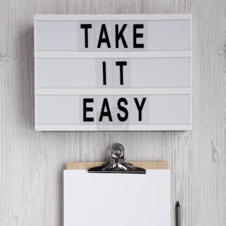 Photo pour 'Take it easy' words on a lightbox, clipboard with blank sheet of paper on a white wooden background, top view. Overhead, from above, flat lay. - image libre de droit