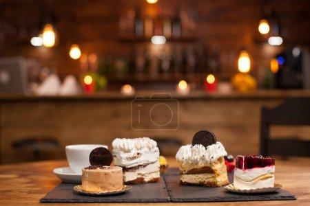 Photo pour Différents gâteaux avec de la crème de pudding sur une table en bois dans un café. Gâteau au pudding avec des fruits rouges frais sur le dessus. Tasse de café savoureux . - image libre de droit