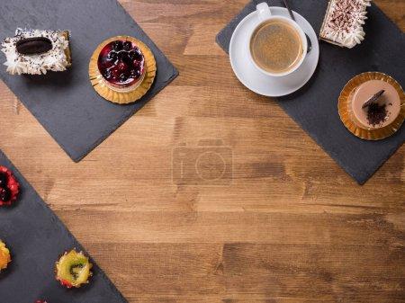Photo pour Top viwe d'une tasse de café avec différents gâteaux aux saveurs différentes sur une table en bois. Gâteaux à la crème de pudding. Gâteau avec crème blanche et biscuit savoureux sur le dessus . - image libre de droit