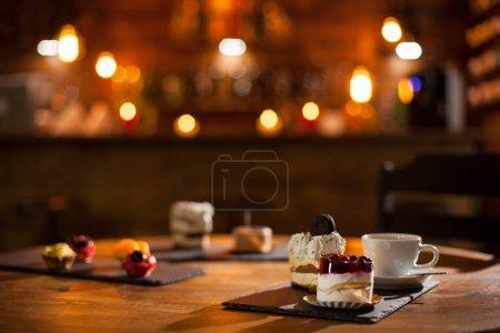 Photo pour Vue magnifique sur différents gâteaux avec différentes saveurs sur une planche en bois dans un café. Délicieuse variété de gâteaux dans un café. Tasse de café savoureux . - image libre de droit