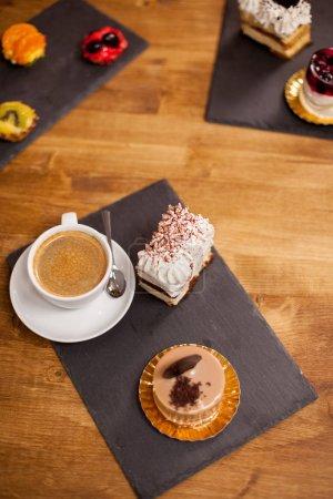 Photo pour Desserts sucrés sur une table en bois dans un café près d'une tasse de café savoureuse. Desserts faits maison dans un café. Gâteau au chocholate savoureux . - image libre de droit
