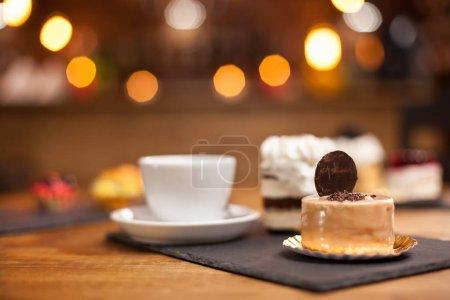 Photo pour Gâteau au chocholate frais avec biscuit sucré sur le dessus dans un café. Petits gâteaux sucrés sur une table en bois dans un café. Délicieux desserts. Spécialités café . - image libre de droit