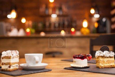 Photo pour Ensemble de différents gâteaux et desserts fraîchement cuits disposés sur une table en bois. Délicieux gâteau avec des fruits naturels sur le dessus. Une tasse de délicieux café. Tranche de gâteau avec biscuit sur le dessus . - image libre de droit