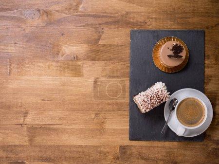 Photo pour Vue du dessus d'une tasse de café près de deux gâteaux chocholate différents sur une table en bois. Délicieux désert. Délicieux gâteau. Des gâteaux frais. Espace de copie disponible . - image libre de droit