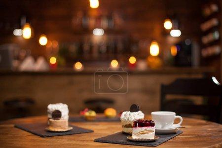 Photo pour Savoureuse tasse de café nouveaux délicieux mini-gâteaux avec différentes formes sur une table en bois - image libre de droit
