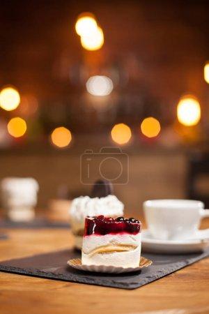 Photo pour Gros plan d'un délicieux mini gâteau avec des fruits sur le dessus d'une table en bois dans un café. Délicieuse tasse de café. Gâteau avec biscuit sur le dessus . - image libre de droit