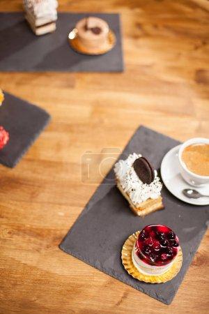 Photo pour Photo du gâteau avec de savoureux biscuits près de différents mini-gâteaux sur une table en bois dans un café. Délicieux gâteau aux fruits savoureux sur le dessus et crème de café . - image libre de droit