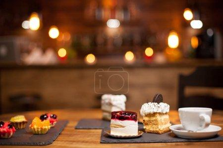 Photo pour Délicieux gâteaux diffrents avec une tasse de café savoureux sur une table en bois dans un café. Photo de gâteaux assortis avec une tasse de café. Délicieux gâteau avec biscuit savoureux sur le dessus . - image libre de droit