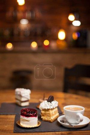 Photo pour Gâteaux assortis pour le dessert sur une table en bois dans un café. Gâteaux aux ingrédients naturels. Délicieuse tasse de café. Gâteaux aux saveurs différentes . - image libre de droit