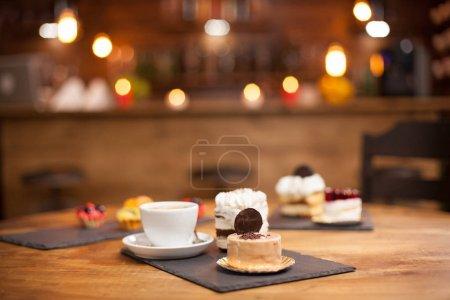 Photo pour Différentes tranches de délicieux gâteaux sur une table en bois dans un café. Tranche de gâteau savoureux avec biscuit sur le dessus. Délicieuse tasse de café . - image libre de droit
