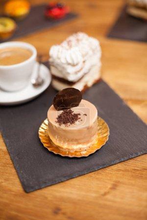 Photo pour Délicieux gâteau avec glaçure brune et délicieux biscuit sur une table en bois dans un café. Délicieux gâteau au goût de cannelle . - image libre de droit