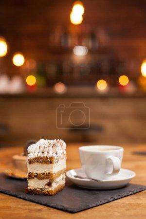 Photo pour Délicieux gâteau au chocholate avec crème blanche et cannelle sur le dessus. Une tasse de délicieux café. Délicieux dessert. Dessert traditionnel avec des ingrédients frais . - image libre de droit