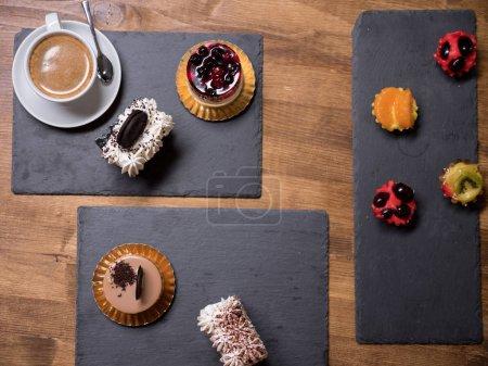 Photo pour Vue de dessus de délicieux gâteaux de différentes saveurs et couleurs sur une table en bois. Délicieux desserts. Desserts frais. Délicieuse tasse de café. Gâteau au pudding différent . - image libre de droit
