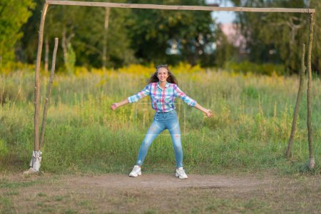 Fun young woman defending a goal standing in an old rustic wooden goalpost with outspread arms grinning at the camera