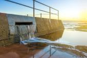 Overflow water flowing out of an ocean beachside pool