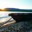 Old fishing boat on the lake at sunset tied with a...