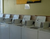 Row of coin operated laundry machines inside a laundromat