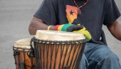 An african themed drummer beating drums at a street performance outside