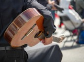 Man cradling acoustic guitar at a street festival before a performance