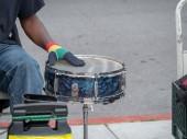Drummer beats on steel drum on sidewalk in a street performance outside