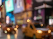 A deliberately defocused shot of yellow taxi cabs zooming through Times Square, New York City with neon signs in the background