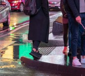A woman walking through Times Square, New York City in rain with puddle reflection on ground of neon lights