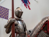An exhibition of 15th century German plate armor around the time of Renaissance. The knight holds a land in his right arm while mounted.