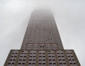 NEW YORK, NY  MAY 19, 2018- Upward view of Empire State Building stretching high above fog and clouds on an overcast day
