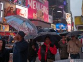 NEW YORK, NY  MAY 16, 2018- Walkers hold umbrellas viewing the neon signs of Times Square on a rainy day