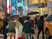 NEW YORK, NY  MAY 16, 2018- Times Square tourists walk past retail stores on a rainy day holding umbrellas
