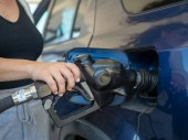 A woman pumping gas with a handheld fuel nozzle at a gas station