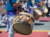 A mexican marching band beats on drums while walking down streets of Carnaval festival
