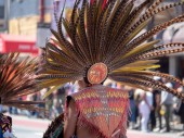 A man wearing traditional Mexican featherwork head dress marches at Carnaval festival