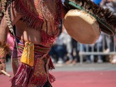A man dressed in traditional Aztec garb beats on a drum during a march