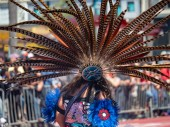 A traditional Mexican featherwork headdress adorned by a woman during a public march