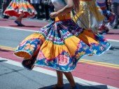 Woman showing dance moves wearing a Mexican fiesta dress at an outdoor march