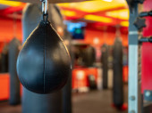 Black leather speedbag, with Muay Thai bags in the back, ready for use in a gym